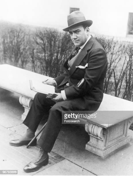 Enrico Caruso sitting on park bench holding book looking into camera circa 1910s