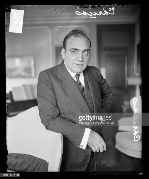 Enrico Caruso standing with one arm resting on the back of chair Chicago Illinois 1920
