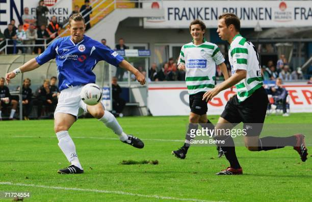 Enrico Kern of Rostock scores the first goal while Juri Judt and Dejan Kelhar of Furth can only watch on during the Second Bundesliga match between...