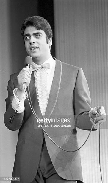 Enrico Macias At The Olympia. Paris - 8 mars 1968 - Sur la scène de l'OLYMPIA, Enrico MACIAS chantant avec un micro.