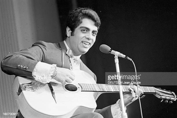Enrico Macias At The Olympia. Paris - 8 mars 1968 - Sur la scène de l'OLYMPIA, Enrico MACIAS chantant en jouant de la guitare.