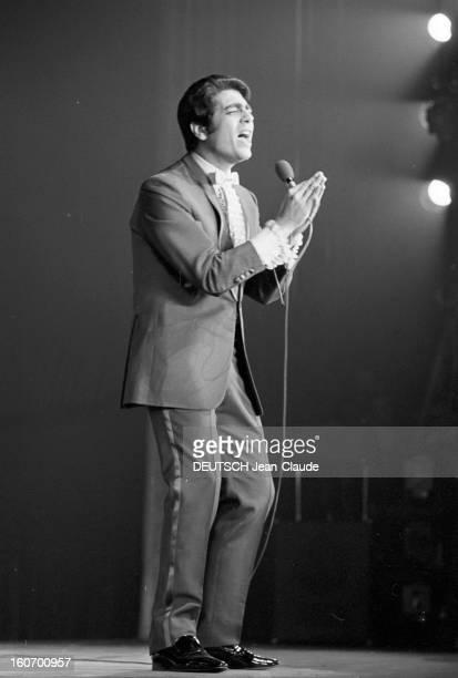 Enrico Macias At The Olympia. Paris - 8 mars 1968 - Sur la scène de l'OLYMPIA, Enrico MACIAS chantant avec un micro dans ses mains jointes.