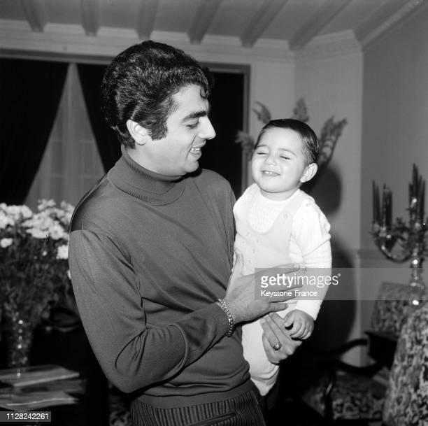 Enrico Macias photographié chez lui avec son fils Jean-Claude dans ses bras, à Paris, France, le 3 décembre 1968.