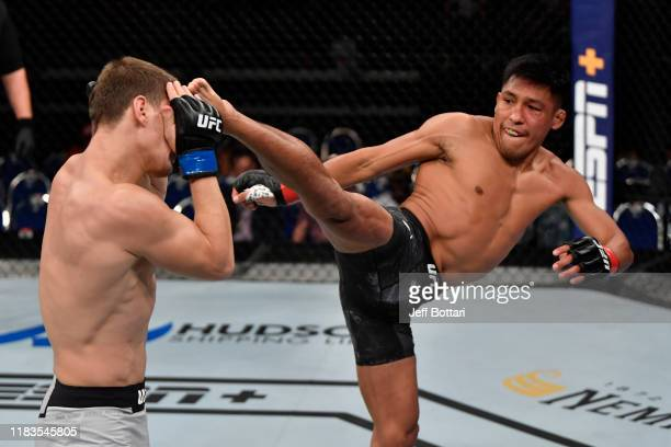 Enrique Barzola of Peru kicks Movsar Evloev of Russia in their featherweight bout during the UFC Fight Night event at Singapore Indoor Stadium on...