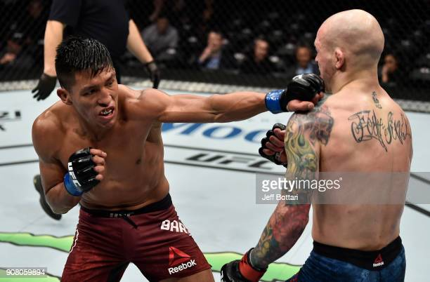 Enrique Barzola of Peru punches Matt Bessette in their featherweight bout during the UFC 220 event at TD Garden on January 20 2018 in Boston...