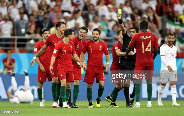 Enrique Caceres shows a yellow card to Cedric of Portugal during the 2018 FIFA World Cup Russia group B match between Iran and Portugal at Mordovia...