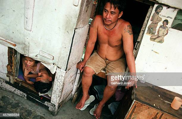 Enrique De La Torre and his girlfriend Mary Joyce Camacho rest in their tiny cell, while Dario Reyes waits for his wife, in the Manila City Jail. The...
