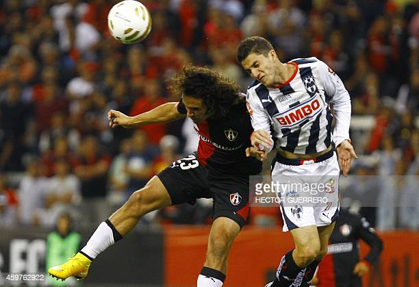 Enrique Esqueda of Atlas vies the ball with Hiram Mier of Monterrey during a quarterfinal football match of 2014 Mexican Apertura tournament football...