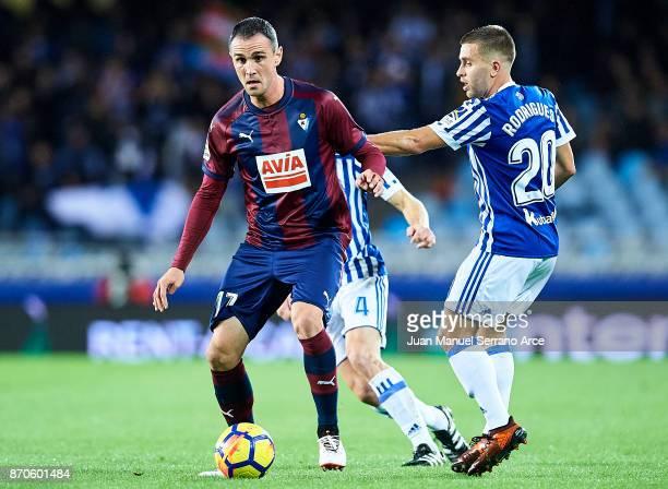 Enrique Garcia of SD Eibar being followed by Kevin Rodrigues of Real Sociedad during the La Liga match between Real Sociedad and Eibar at Estadio...