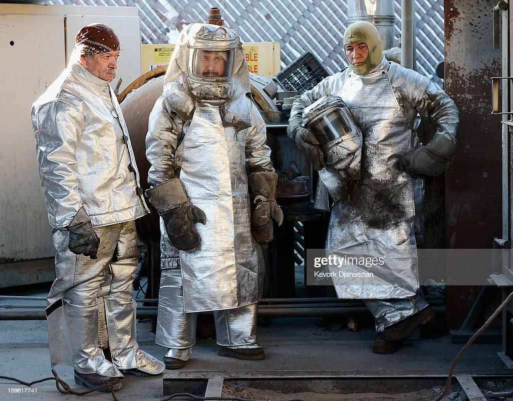 Enrique Guerrero (L) Adalid Orozco (C) and Jose Sosa done fire suits to protect themselves from heat before pouring molten bronze metal into molds as during the casting of the Screen Actors Guild Award statuettes, at the American Fine Arts Foundry on January 17, 2013 in Burbank, California. The 19th Annual SAG Awards, which honors outstanding motion picture and primetime television performances are to be held in Los Angeles on January 27.