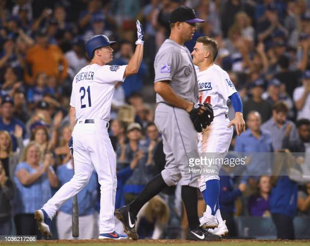 Enrique Hernandez and Walker Buehler of the Los Angeles Dodgers celebrate a run in front of Tyler Anderson of the Colorado Rockies to tie the game 22...