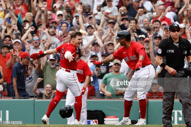 Enrique Hernandez of the Boston Red Sox is congratulated by Rafael Devers after scoring the go ahead run during the eighth inning of their 5-4 win...