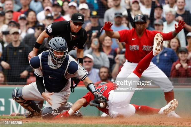 Enrique Hernandez of the Boston Red Sox slides home safely ahead of the tag by catcher Gary Sanchez of the New York Yankees to score the go ahead run...