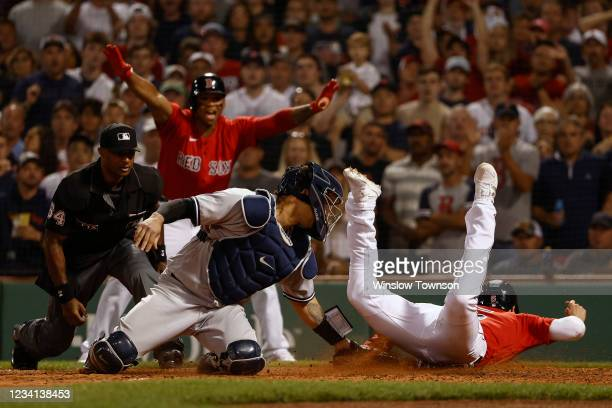Enrique Hernandez of the Boston Red Sox slides safely into home as catcher Gary Sanchez of the New York Yankees applies a late tag while umpire Alan...
