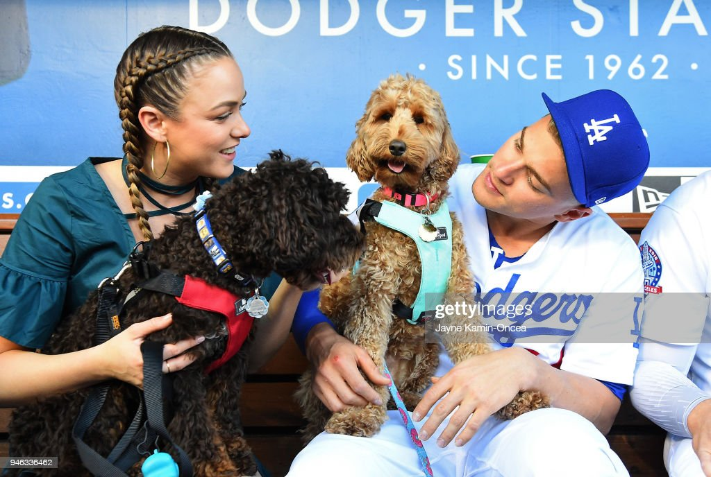 Enrique Hernandez #14 of the Los Angeles Dodgers and his wife Mariana Hernandez, hold their dogs Arizona and Bruce Wayne, in the dugout during 'Pups at the Park' before the game against the Arizona Diamondbacks at Dodger Stadium on April 14, 2018 in Los Angeles, California. At today's game, fans walked in a pre-game pup parade on the field and were able to sit in the stands with their dogs.