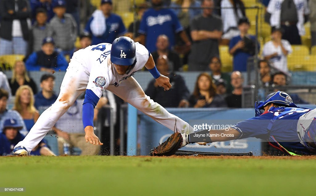 Enrique Hernandez #14 of the Los Angeles Dodgers beats the tag by Carlos Perez #60 of the Texas Rangers in the eleventh inning at Dodger Stadium on June 13, 2018 in Los Angeles, California.