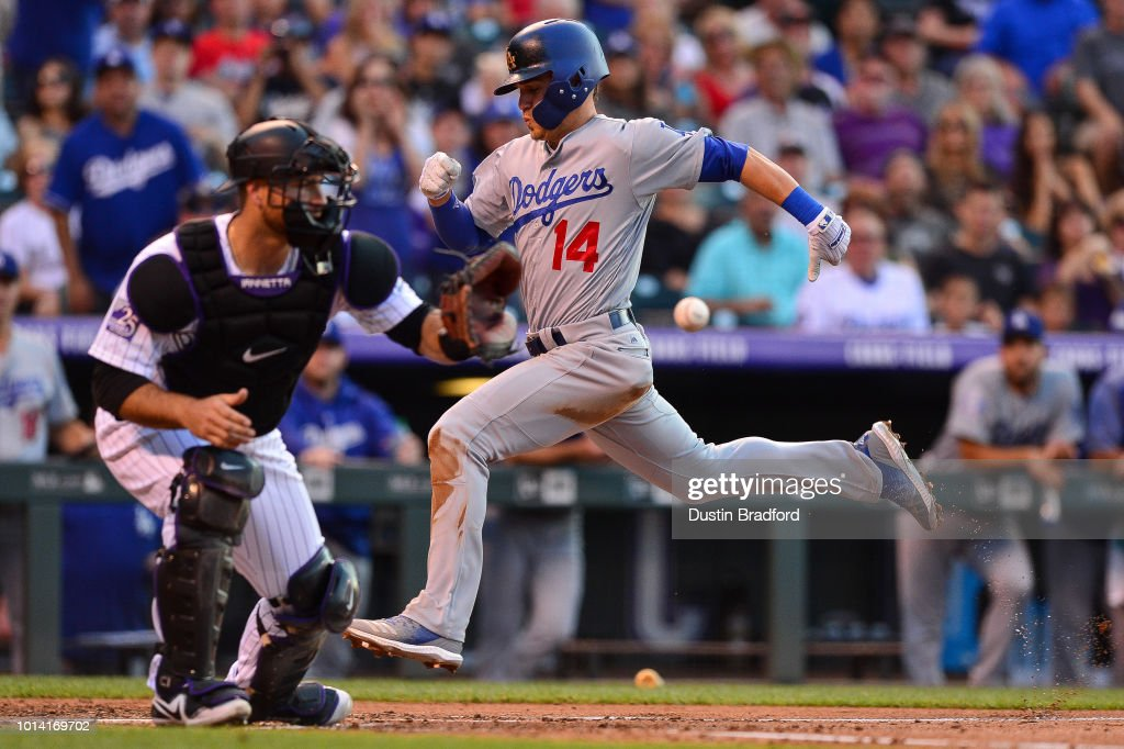 Enrique Hernandez #14 of the Los Angeles Dodgers beats the throw to Chris Iannetta #22 of the Colorado Rockies to score a run on a sacrifice fly in the second inning of a game at Coors Field on August 9, 2018 in Denver, Colorado.