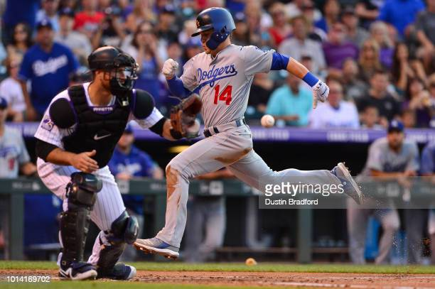 Enrique Hernandez of the Los Angeles Dodgers beats the throw to Chris Iannetta of the Colorado Rockies to score a run on a sacrifice fly in the...