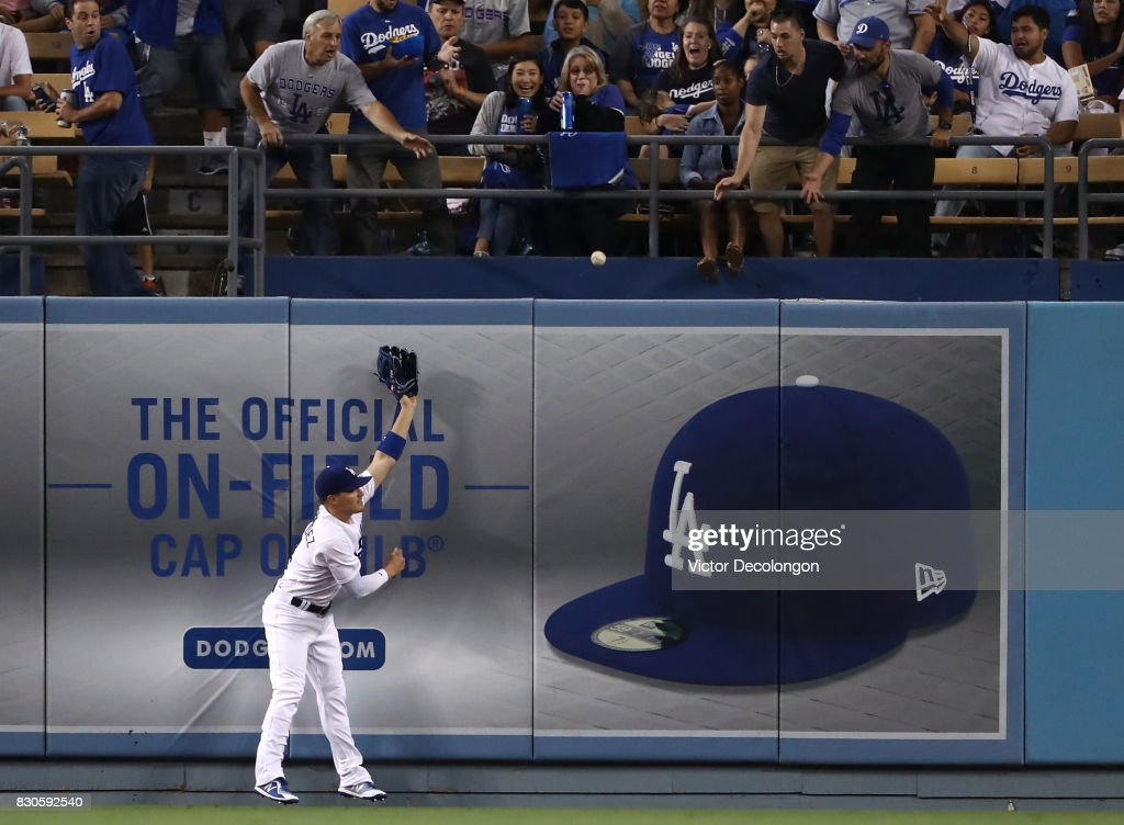 Enrique Hernandez #14 of the Los Angeles Dodgers can't make the catch at the center field wall on a homerun ball hit by Manuel Margot #7 of the San Diego Padres in the third inning during the MLB game at Dodger Stadium on August 11, 2017 in Los Angeles, California.