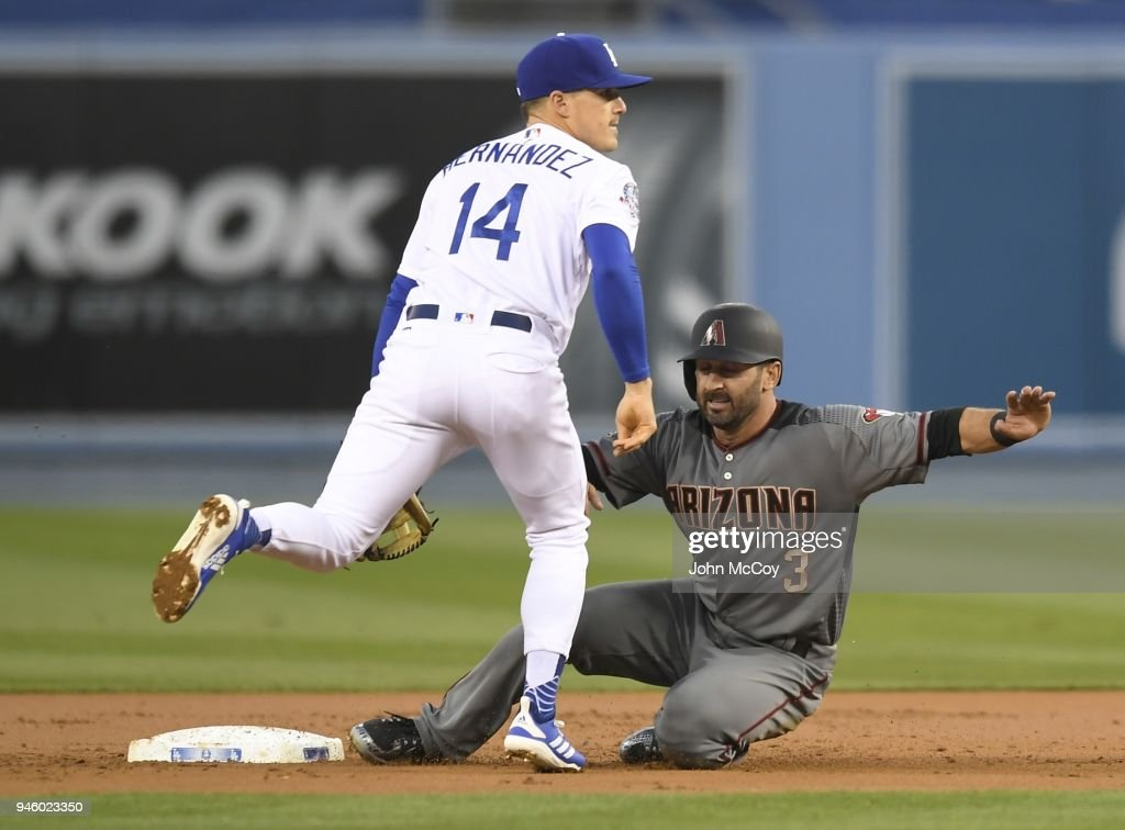 Enrique Hernandez #14 of the Los Angeles Dodgers catches Daniel Descalso #3 of the Arizona Diamondbacks out at second base on a double play in the first inning at Dodger Stadium on April 13, 2018 in Los Angeles, California.