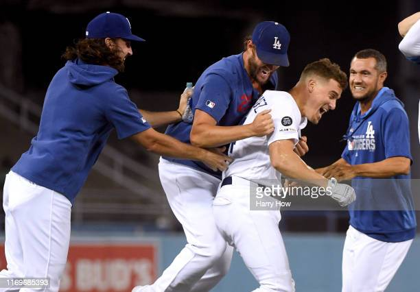Enrique Hernandez of the Los Angeles Dodgers celebrates his walk off single with Tony Gonsolin Clayton Kershaw and Kristopher Negron for a 32 win...