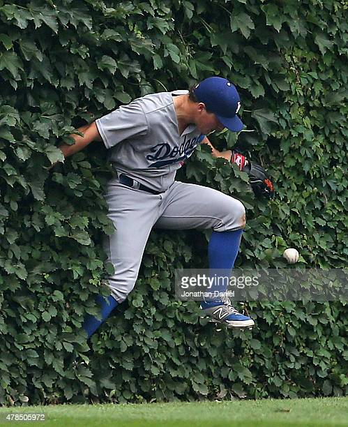 Enrique Hernandez of the Los Angeles Dodgers drops the ball after hitting the outfield wall in the 5th inning on a double by Anthony Rizzo of the...