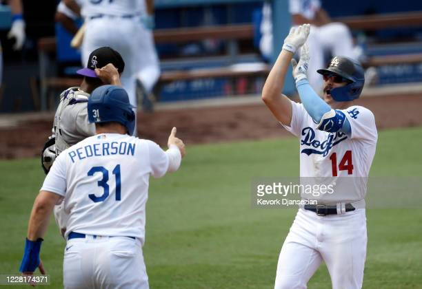 Enrique Hernandez of the Los Angeles Dodgers gestures as if he is taking a basketball shot as he celebrates his three run hone run with Joc Pederson...