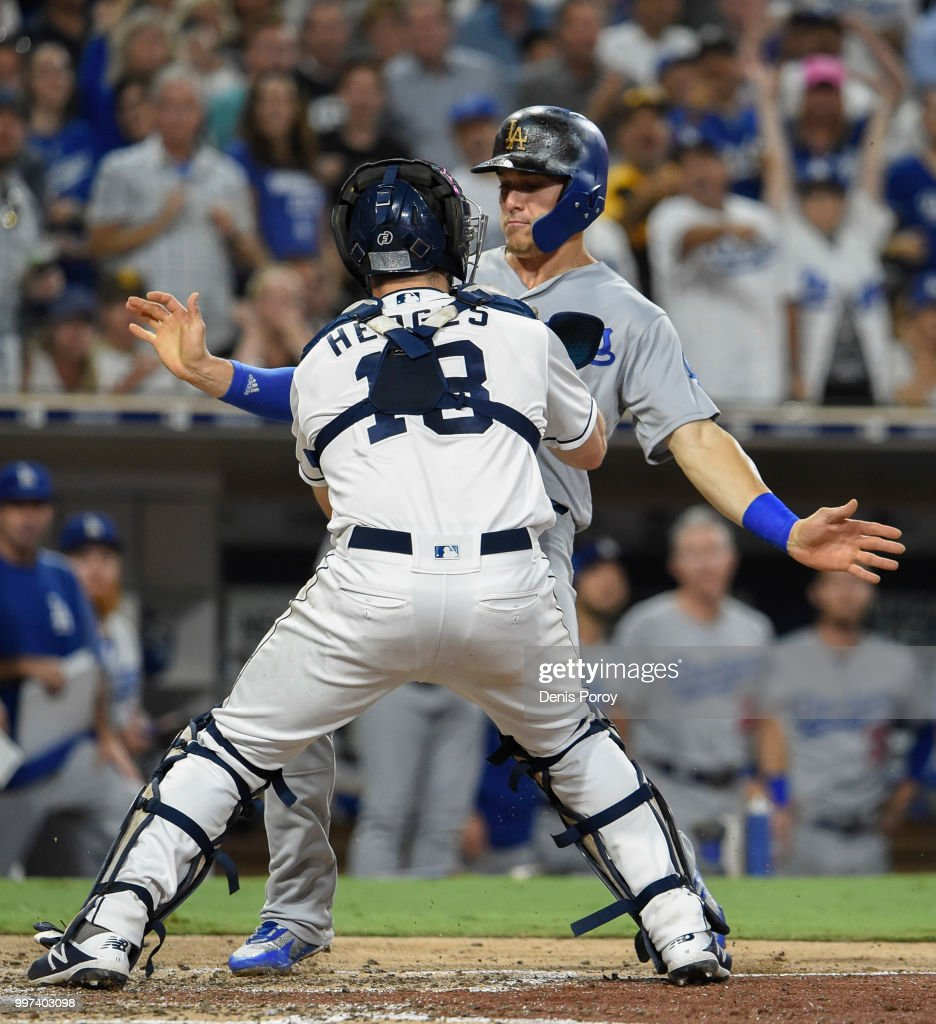 Enrique Hernandez #14 of the Los Angeles Dodgers is tagged out at the plate by Austin Hedges #18 of the San Diego Padres during the seventh inning of a baseball game at PETCO Park on July 12, 2018 in San Diego, California.