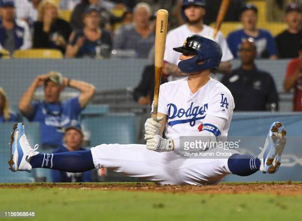 Enrique Hernandez of the Los Angeles Dodgers lands in the dirt after backing off a high pitch in the eighth inning of the game against the Miami...