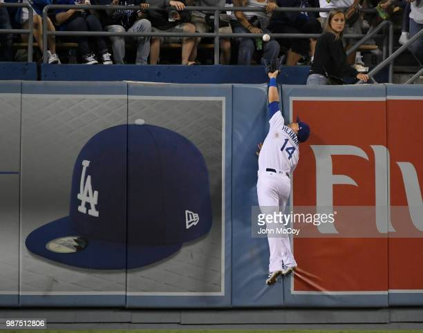 Enrique Hernandez of the Los Angeles Dodgers leaps but can not catch a home run ball hit by Pat Valaika of the Colorado Rockies in the fifth inning...