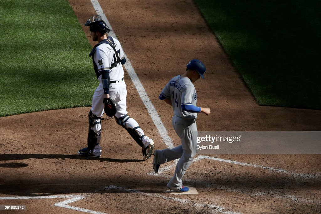 Enrique Hernandez #14 of the Los Angeles Dodgers scores a run past Jett Bandy #47 of the Milwaukee Brewers in the sixth inning at Miller Park on June 3, 2017 in Milwaukee, Wisconsin.