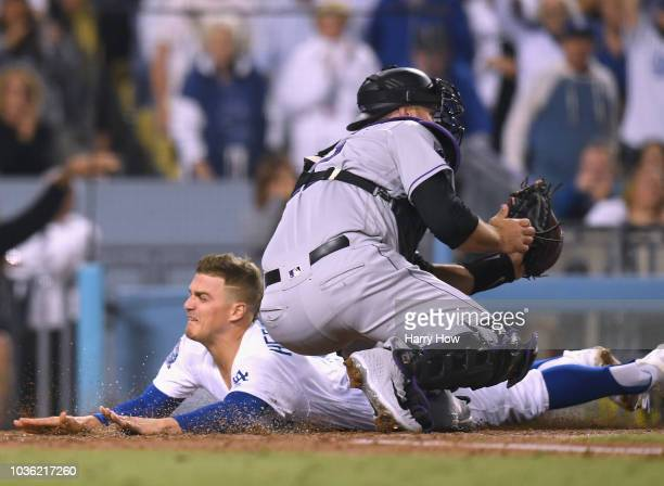 Enrique Hernandez of the Los Angeles Dodgers scores in front of Chris Iannetta of the Colorado Rockies to tie the game 22 during the fifth inning at...