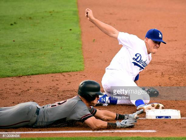 Enrique Hernandez of the Los Angeles Dodgers slides at first for an out of Jake Lamb of the Arizona Diamondbacks to end the second inning at Dodger...