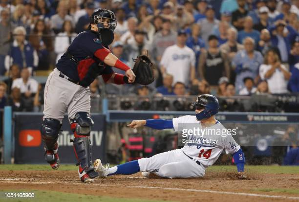 Enrique Hernandez of the Los Angeles Dodgers slides into home plate as catcher Christian Vazquez of the Boston Red Sox throws to first base after...