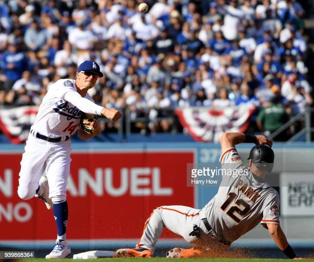 Enrique Hernandez of the Los Angeles Dodgers turns a double play over Joe Panik of the San Francisco Giants during the first inning on the 2018 Major...