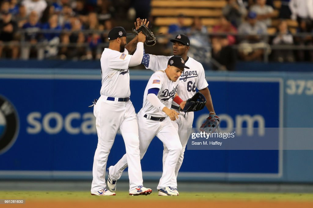 Enrique Hernandez #14, Yasiel Puig #66 and Matt Kemp #27 of the Los Angeles Dodgers celebrate defeating the Pittsburgh Pirates 8-3 in a game at Dodger Stadium on July 3, 2018 in Los Angeles, California.