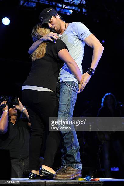 Enrique Iglesias invites fan Stephanie Pochino on stage as he performs during the Y100 Jingle Ball at BankAtlantic Center on December 11 2010 in...