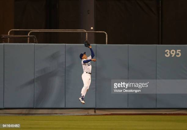 Enrique 'Kike' Hernandez of the Los Angeles Dodgers jumps to make a catch on a fly ball to deep center field during the ninth inning of the MLB game...