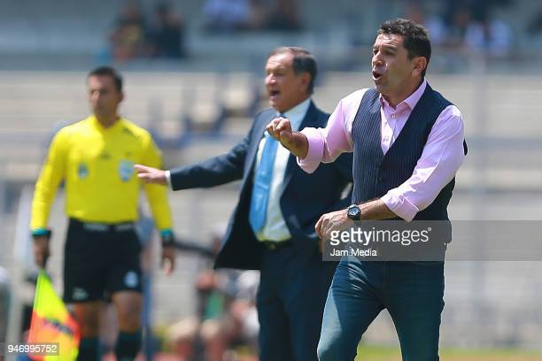 Enrique Meza coach of Puebla and David Patiño coach of Pumas react during the 15th round match between Pumas UNAM and Puebla as part of the Torneo...