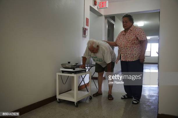 Enrique Padilla and Frances Padilla cook their lunch in the hallway where there is a working power outlet at the Pedro America Pagan de Colon...