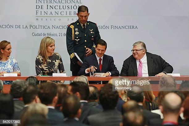 Enrique Pena Nieto Mexico's president center signs a paper as Agustin Carstens governor of Mexico's central bank Banco de Mexico right Queen Maxima...