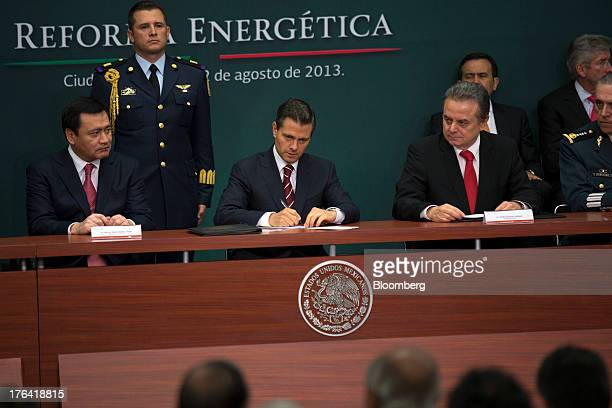 Enrique Pena Nieto Mexico's president center signs a proposed energy reform bill during an announcement with Miguel Angel Osorio Chong minister of...