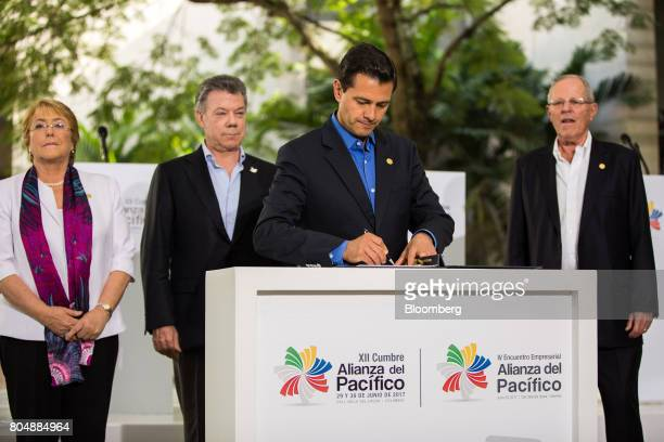 Enrique Pena Nieto Mexico's president center signs an agreement as Michelle Bachelet Chile's president left Juan Manuel Santos Colombia's president...