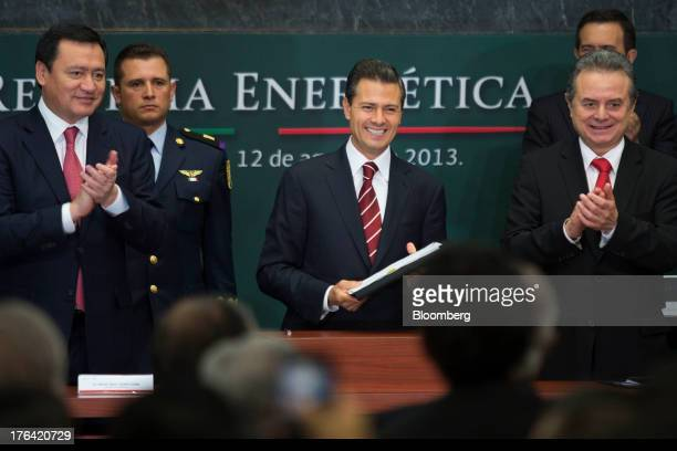 Enrique Pena Nieto Mexico's president center smiles after signing a proposed energy reform bill during an announcement with Miguel Angel Osorio Chong...