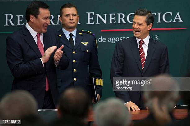 Enrique Pena Nieto Mexico's president right and Miguel Angel Osorio Chong minister of the interior left smile during an announcement on energy reform...