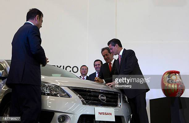 Enrique Pena Nieto Mexico's president right signs a Nissan Motor Co vehicle during the opening ceremony for a new plant with Carlos Ghosn chief...