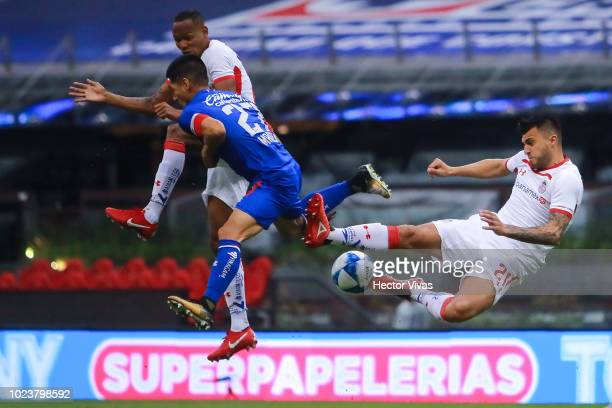 Enrique Triverio and Luis Quinones of Toluca jump for the ball against Jose Maduena of Cruz Azul during the 6th round match between Cruz Azul and...