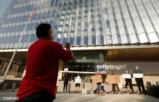 Enrique Velasquez left takes a photo of about a dozen protestors from West Valley Peoples Alliance gathered in front of Los Angeles federal...
