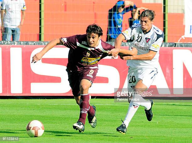Enrique Vera of Ecuador's Liga Deportiva Universitaria vies for the ball with Eduardo Salvio of Argentina's CA Lanus during their Copa Sudamericana...