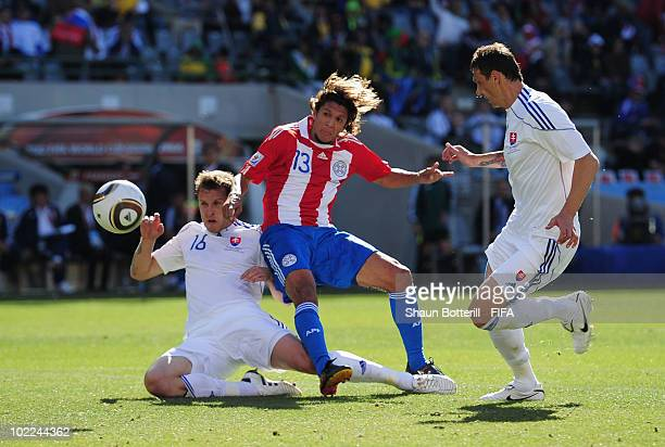 Enrique Vera of Paraguay scores the opening goal while Jan Durica and Kornel Salata of Slovakia try to defend during the 2010 FIFA World Cup South...